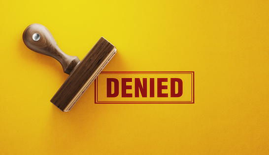Wooden denied stamp on yellow background. Horizontal composition with copy space.