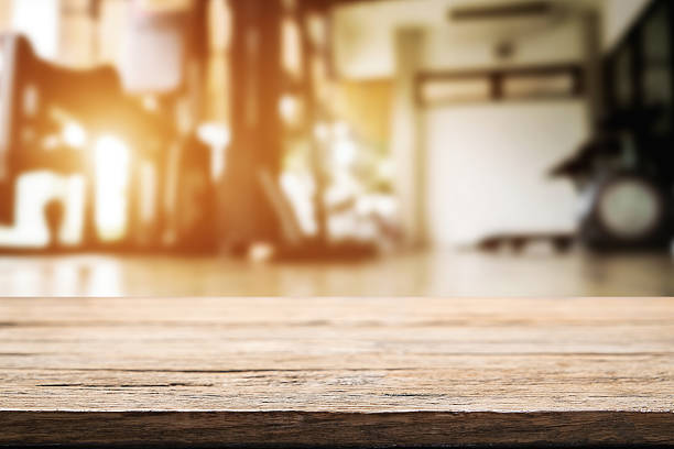 Wooden desk space and fitness gym background – Foto