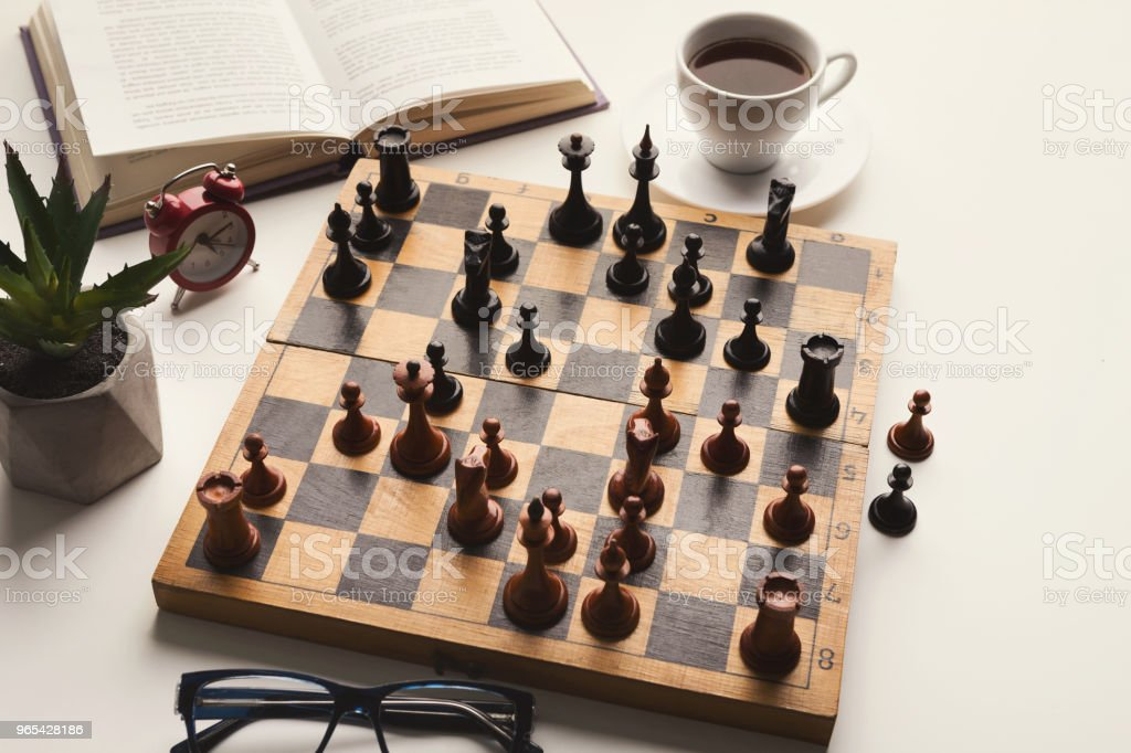 Wooden desk with chess play, book and coffee cup royalty-free stock photo