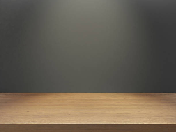 wooden desk with gray wall under light - front view stock photos and pictures