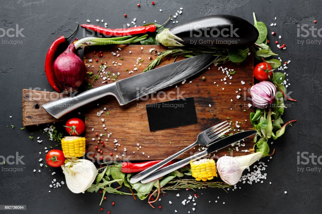 Wooden desk with vegetables border on dark background stock photo