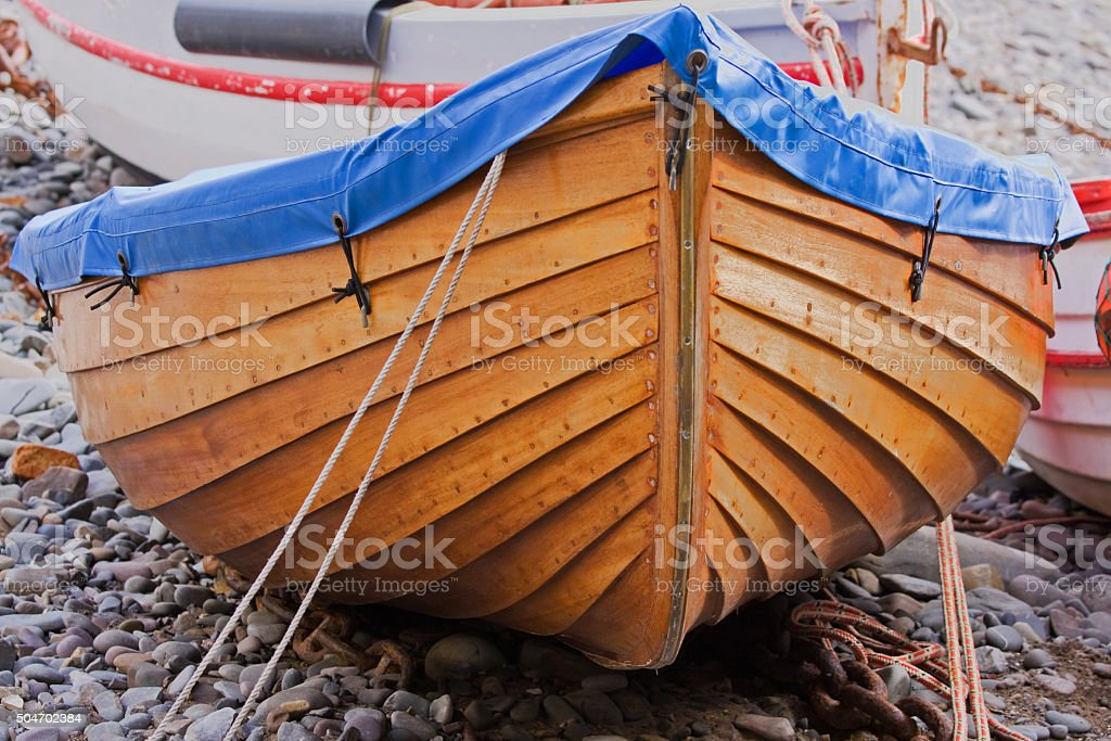 Wooden dinghy laid up ashore in winter UK stock photo