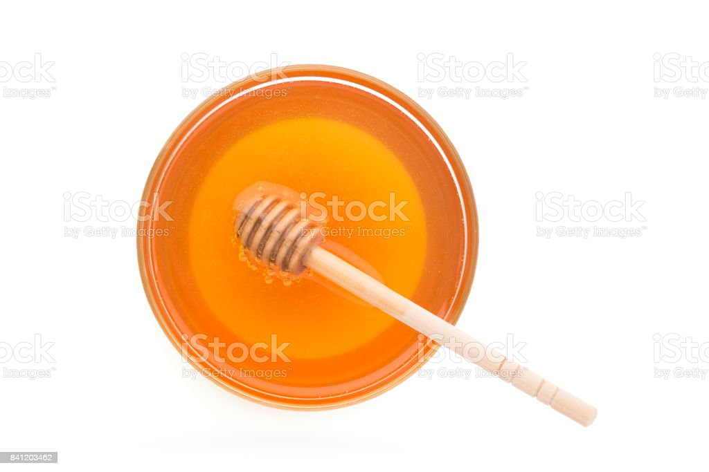 Wooden dipper with bowl of honey, isolated on the white background stock photo