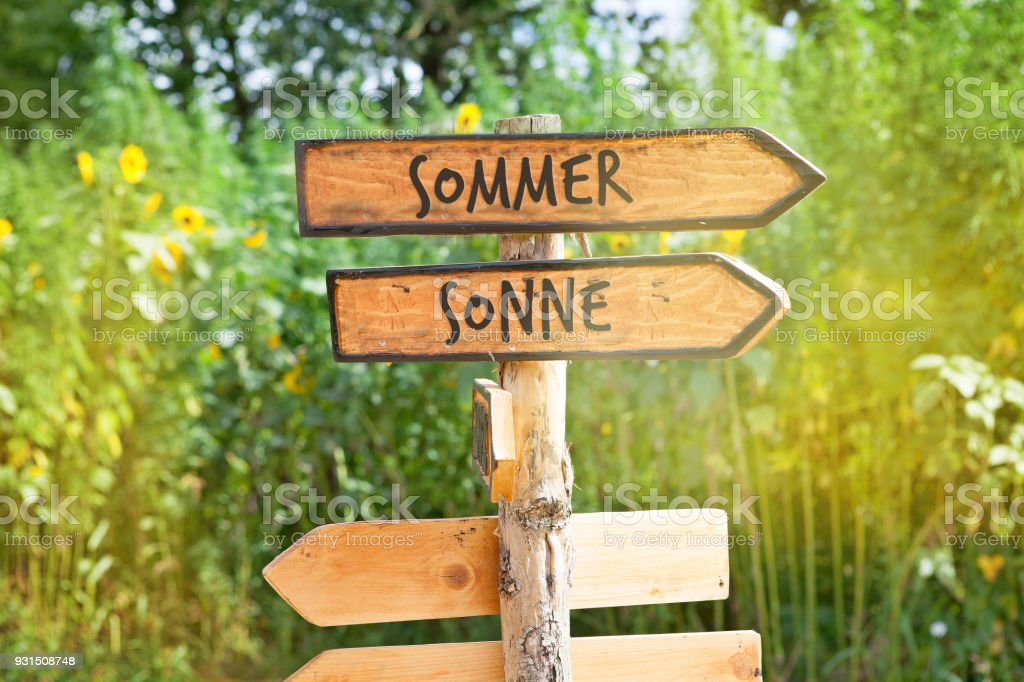 Wooden direction sign with the German words summer and sun (Sommer, Sonne) stock photo