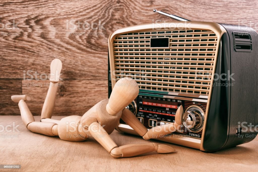 Wooden doll enjoy listening to music while lying near the radio...