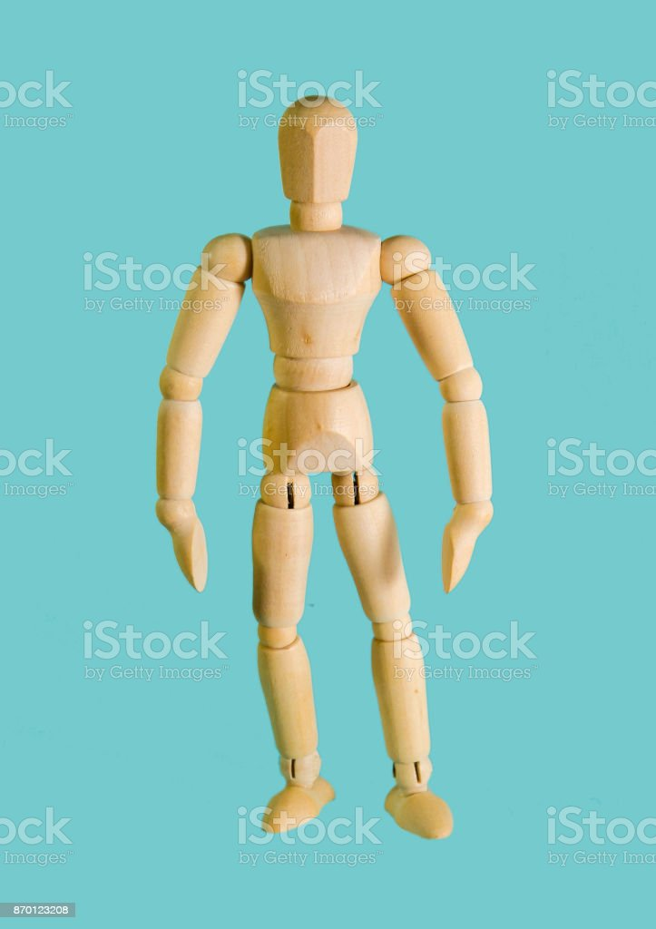 wooden doll stands on a blue background close-up stock photo
