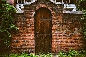 An Old Wooden Door in a Worn Brick Facade