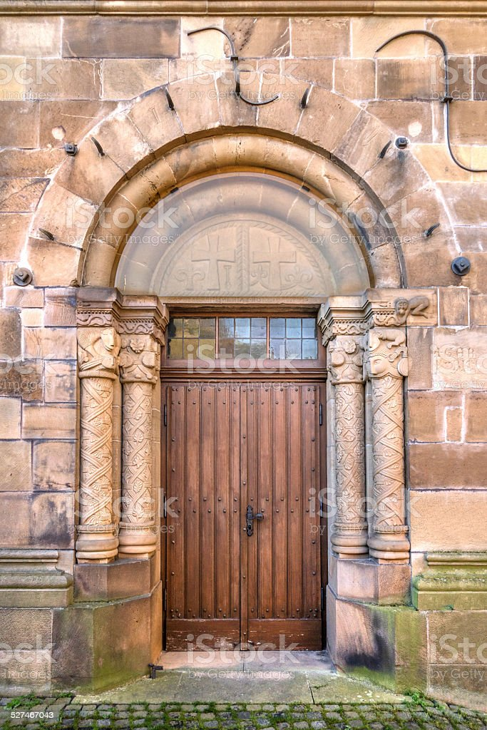 Wooden door in a romanesque stepped portal royalty-free stock photo