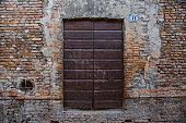 Wooden door in a worn facade made of bricks
