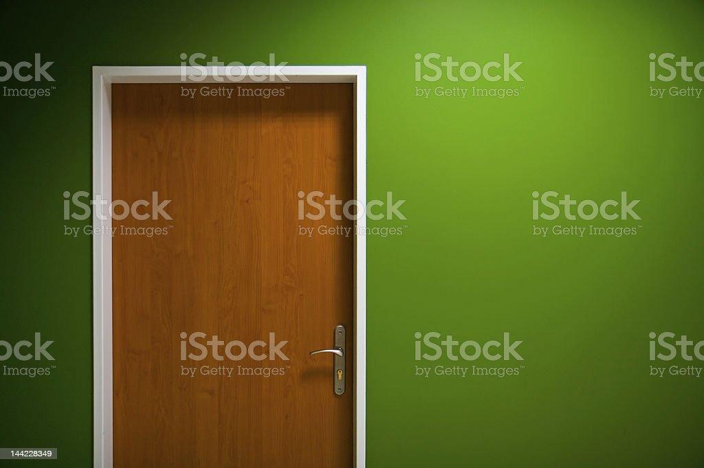 Wooden door on green background stock photo