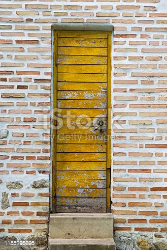 Old yellow wooden door on a brick and rocks wall