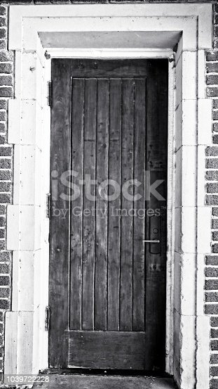 New Orleans, LA USA - May 9, 2018  -  Wooden Door White Doorway in a Red Brick Building B&W