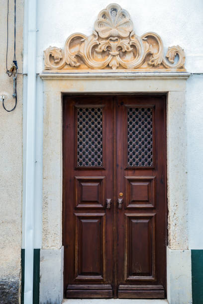 A wooden door with great ornaments above it A wonderful wooden door with ornaments above it on the wall in a village in Portugal. war effort stock pictures, royalty-free photos & images