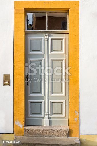 istock Wooden door with ornaments and ornaments and skylight of a restored half-timbered house with brushed sandstone frame 1124400673
