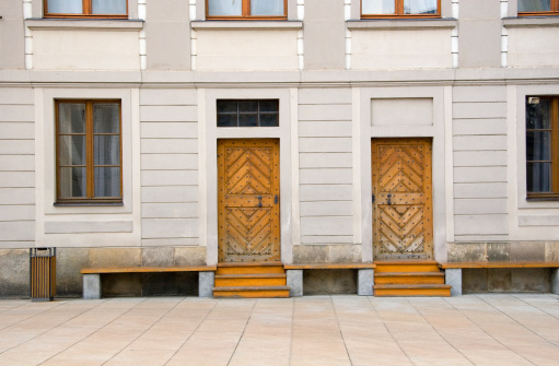 Wooden Doors On White Building Stock Photo - Download Image Now