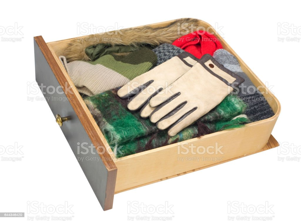 Wooden drawer of a dresser with warm winter clothes - gloves, scarf,  cap, fur collar. Isolated with patch stock photo