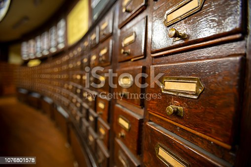 Wooden drawers with metal ornaments in an old-fashioned library. Wooden boxes with index cards in library.