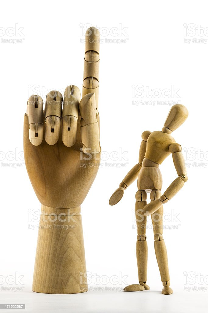 Wooden dummy looks at big hand with raised finger royalty-free stock photo