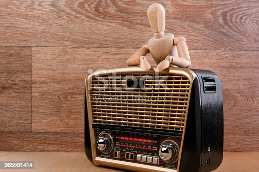 Wooden dummy stands in relaxed pose behind the radio receiver in retro style with audio player putting his hands on it