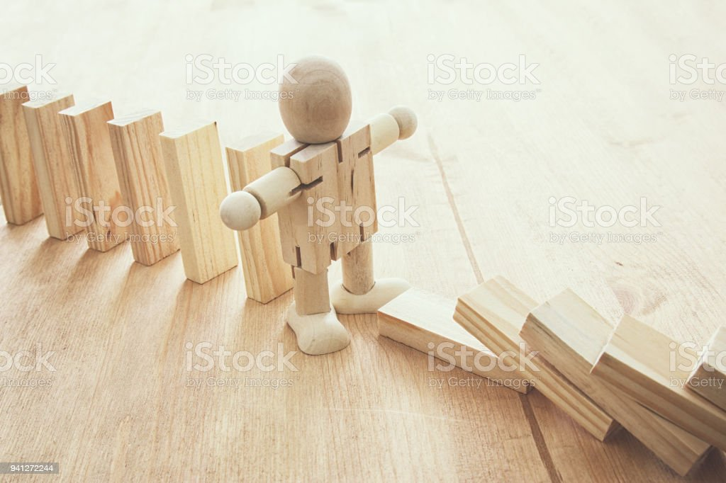A wooden dummy stopping the domino effect. retro style image executive and risk control concept. royalty-free stock photo