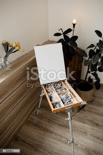 istock Wooden easel for the artist with a canvas and pastel colors in white loft interior in scandinavian style 657270888