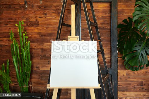 671393252 istock photo Wooden easel in the room 1144776375