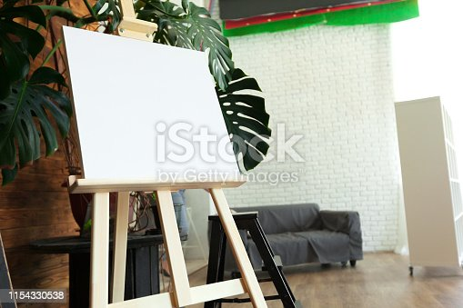 671393252 istock photo Wooden easel in the room 1154330538