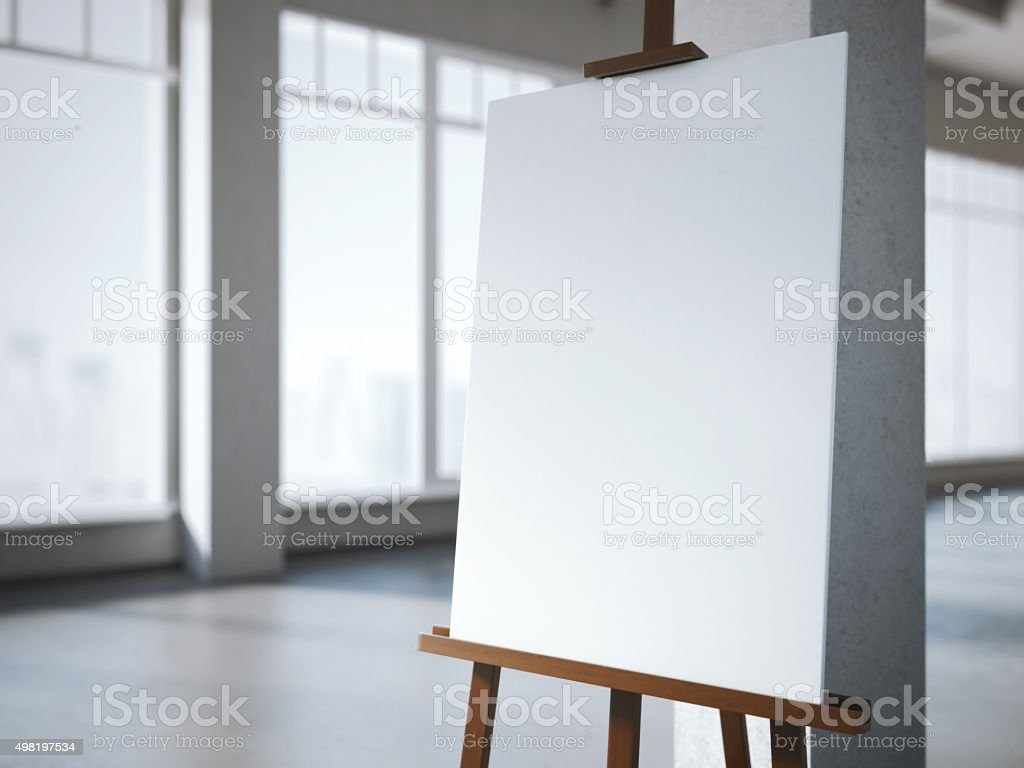 Wooden easel with a blank white canvas in modern interior. stock photo