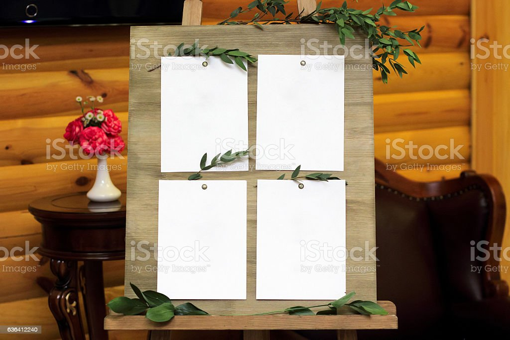 Wooden easel with a board. On board attached white sheets stock photo