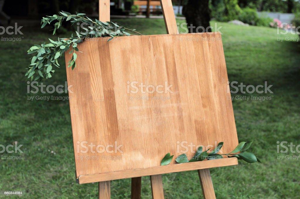 Hölzerne Staffelei mit einem Brett. An die Tafel geschrieben Weißlack - willkommen – Foto