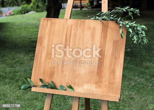 671393252istockphoto Wooden easel with a board. On the board written white paint - Welcome 665571796