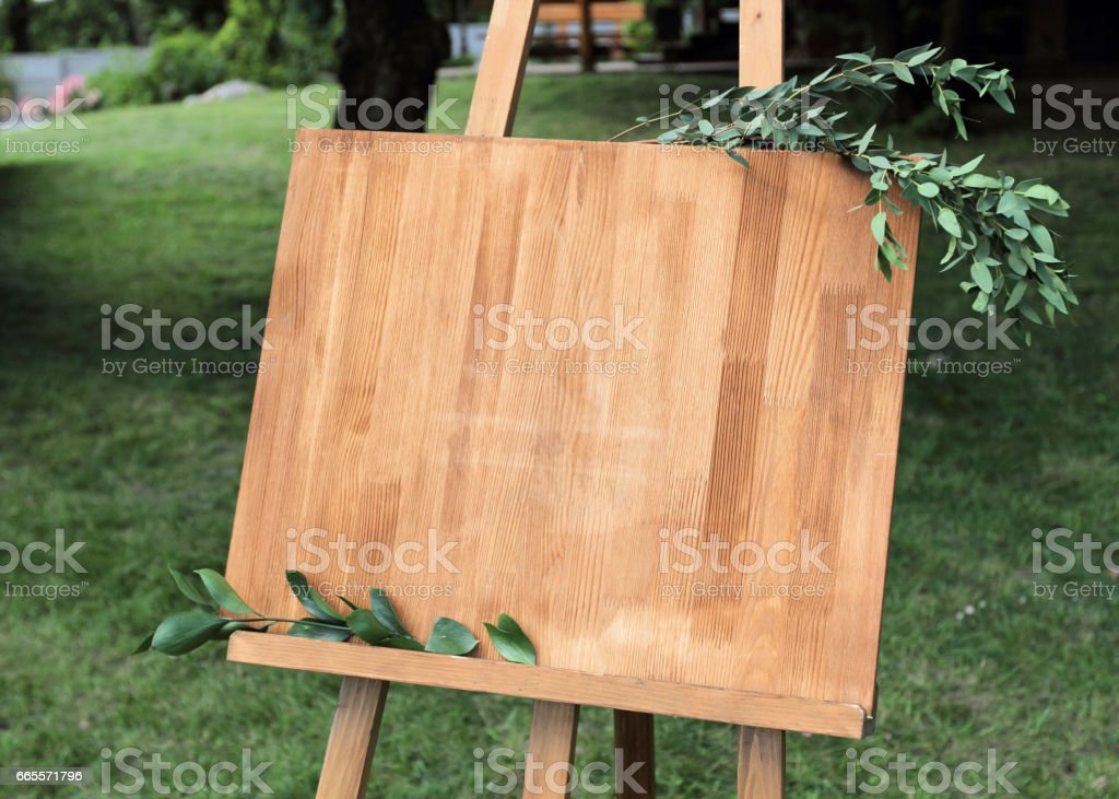 Wooden easel with a board. On the board written white paint - Welcome stock photo