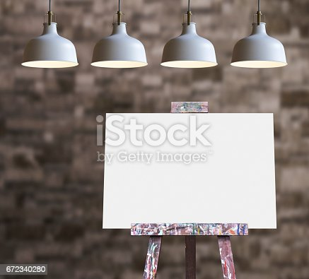 671393252istockphoto Wooden easel with blank painting canvas in the room 672340280