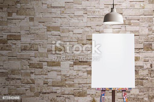 671393252istockphoto Wooden easel with blank painting canvas in the room 672340466