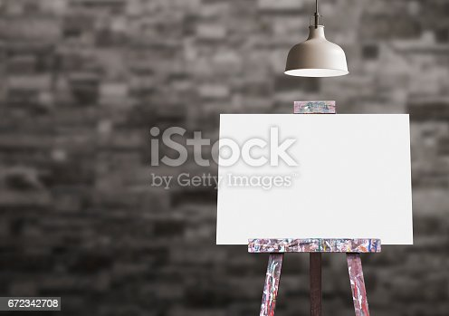 istock Wooden easel with blank painting canvas in the room 672342708