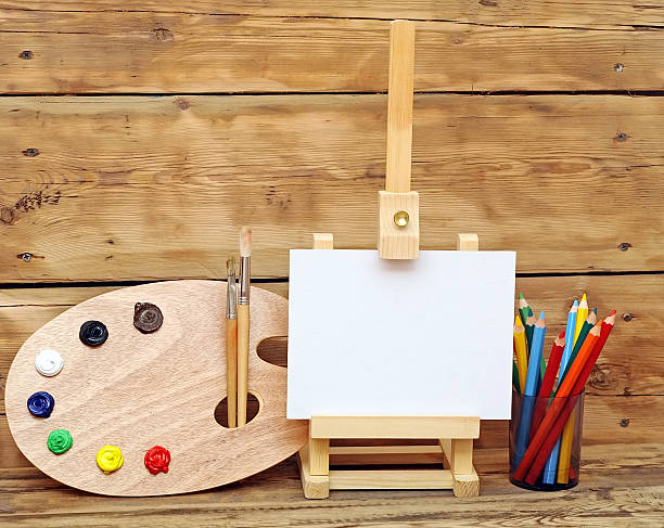 Wooden easel with clean paper and artistic equipment stock photo