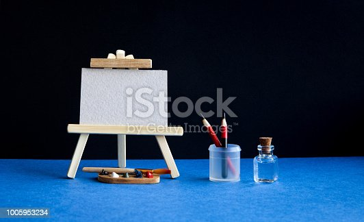 istock Wooden easel with textured blank paper canvas on black wall blue floor background. Beautiful art class studio tools. Palette watercolor brushes, pencils in a case and water 1005953234
