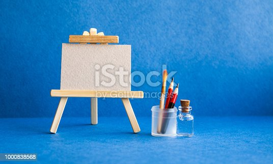 istock Wooden easel with textured blank paper canvas on blue background. Beautiful art class studio interior, watercolor brushes, pencils in a case, water. Artist's advertising poster mockup 1000838568