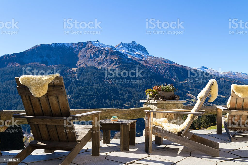 Wooden easy chairs at a mountain lodge terrace, Klosters Switzer stock photo