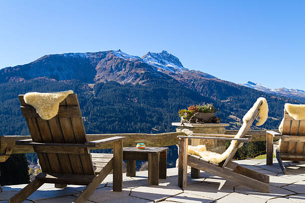 Wooden easy chairs at a mountain lodge terrace, Klosters Switzer Wooden easy chairs at a mountain lodge terrace with panoramic view of beautiful alpine landscape in autumn at the Klosters - Davos region, Switzerland. chalet stock pictures, royalty-free photos & images