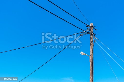 Wooden electric pole with street lamp in Greece.