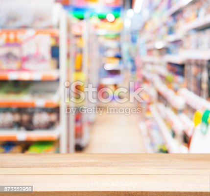 926078666 istock photo Wooden empty table in front of of kids toy store 872552956