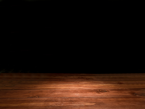 Wooden empty table (reddish brown rustic wood) with spotlight. Dark (black) background. Ideal for photo montage. No people. Horizontal orientation.