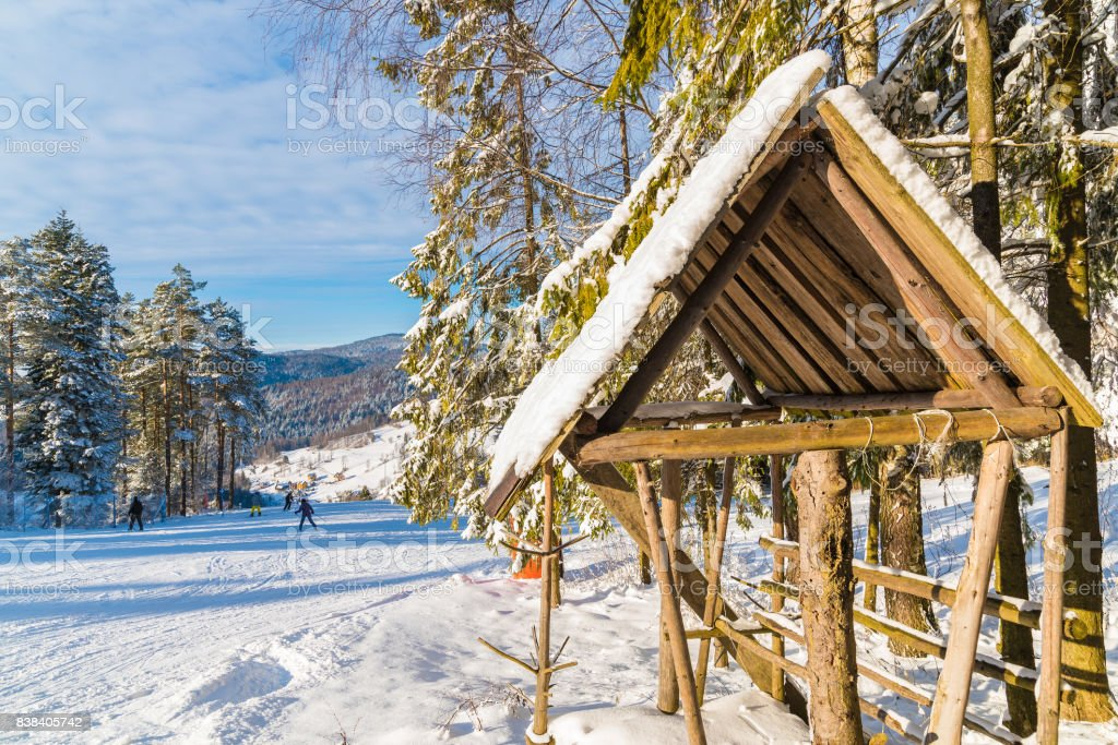 Wooden feeding rack in Beskid Sadecki Mountains on sunny winter day, Poland stock photo
