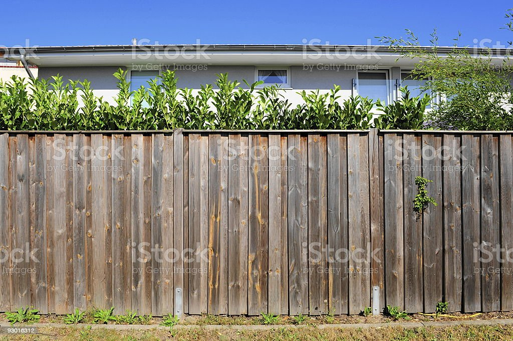 A wooden fence along someone's house royalty-free stock photo