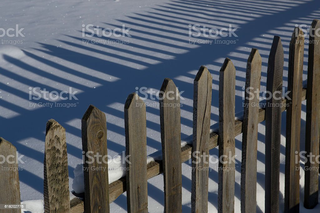 Wooden fence and shadow on the snow. stock photo
