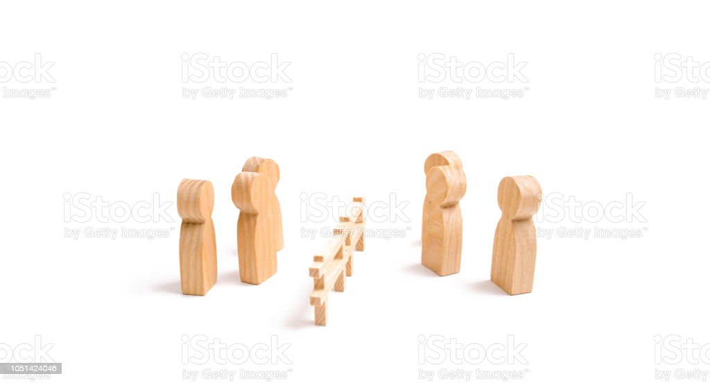 A wooden fence divides the two groups discussing the case. Termination and breakdown of relations, breaking ties. Contract break, conflict of interests. Negotiations of businessmen. stock photo