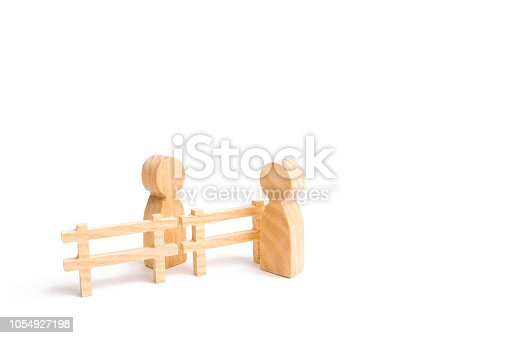 656916072istockphoto A wooden fence divides the two groups discussing the case. Termination and breakdown of relations, breaking ties. Contract break, conflict of interests. Negotiations of businessmen. 1054927198