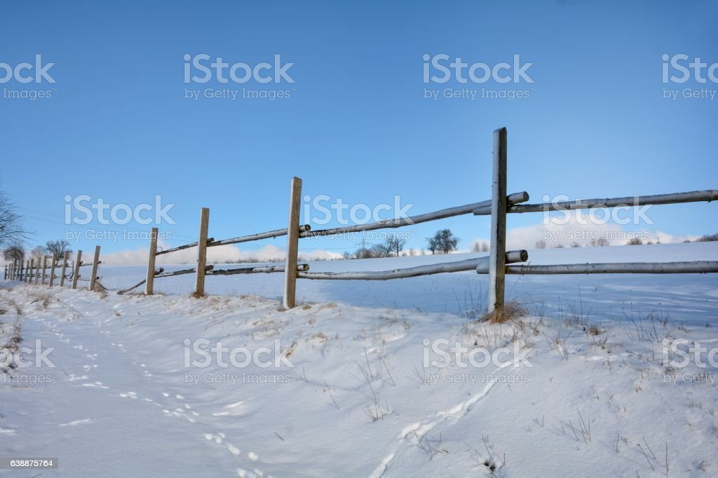 Wooden fence in winter with snow and blue sky stock photo
