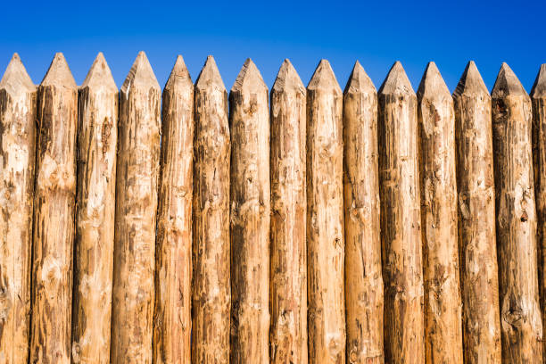 wooden fence made of sharpened planed logs - palisade boundary stock photos and pictures